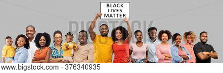 civil rights, equality and anti-racism protest concept - group of happy smiling african american people with black lives matter banner over grey background