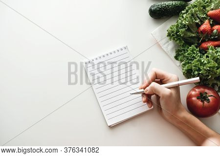 Woman Makes Notes In A Notebook, Food Shopping List Or Writing Recipes. Mock Up. High Quality Photo