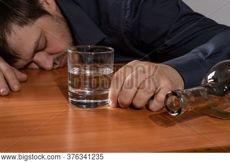 A Man In Alcoholic Intoxication Holds A Glass Of Alcohol. Alcoholism, Addiction, Delirium