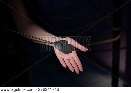 An Unrecognizable Woman Demonstrates An Elegant Thin Leather Strip Whip In A Dark Bedroom. Close-up