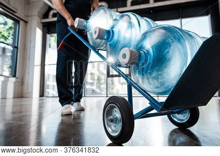 Cropped View Of Delivery Man In Uniform Holding Hand Truck With Purified Water In Bottles