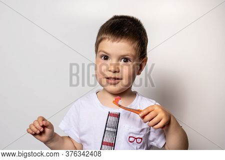 A Little Boy Holds An Orange Toothbrush With Toothpaste. The Child Brushes His Teeth, Prevention Of