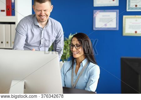 Portrait Of Smiling Worker Involved In Process. Cheerful Middle-aged Man And Pretty Young Woman Usin