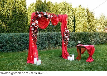 Wedding. Ceremony. Wedding Arch. Red Wedding Arch Of Flowers And Greenery Stands On The Green Grass