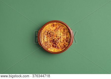 Bowl Of Crème Brûlée With Caramel Crust, In A Clay Tray, On Green Background. Top View Of Homemade B