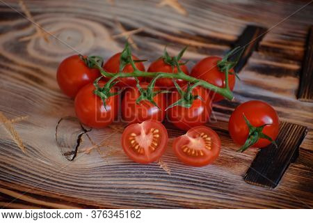 Fresh Sprig Of Ripe Cherry Tomatoes Next To Cut Tomatoes On Brown Rustic Wooden Table. Ingridient Fo