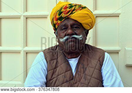 Jodhpur, Rajasthan, India, Circa 2020. A Sad Old Man Cum Gatekeeper Wearing A Yellow Colorful Turban