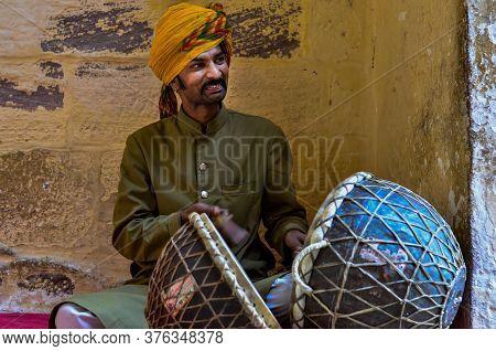 Jodhpur, Rajasthan, India, 2020. Traditional Rajasthani Drum Player Wearing Yellow Pagdi Playing Dru