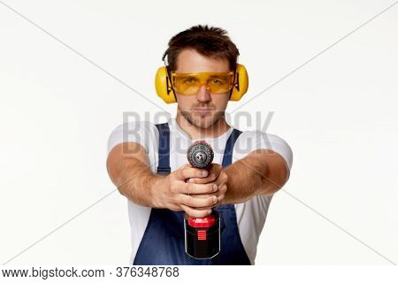 Caucasian Repairman Worker In Uniform, Safety Glasses And Headphones Holding Cordless Screwdriver Is