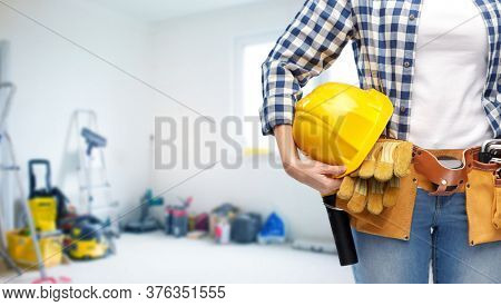repair, construction and building concept - close up of woman or builder with helmet and working tools on belt over utility room background