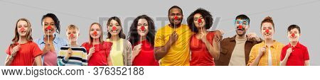 charity and red nose day concept - group of happy smiling people with clown noses hugging over grey background