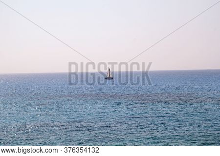 Lonely Ship, Sailboat At Open Sea. Calm Sea Allows Best Sailing In Peaceful Scene. Little Sailing Bo