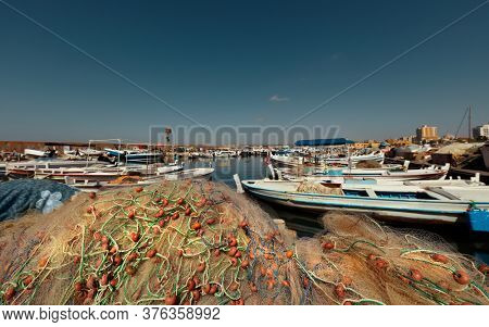 Beautiful Sunny Day. Port of Fishing Boats with Pile of Fishing Nets. Traditional Summer Job of a Coastal Towns.