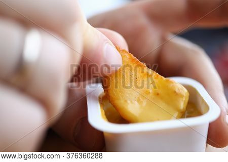 Close-up Of Male Hand Holding Dipping Potatoes And Sauce In Plastic Container. Yummy Snack For Quick