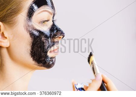 Woman Applying Black Mask To Skin Face