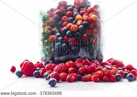 On A White Background. Glass Jar. Freshly Picked Blueberries, Raspberries And Wild Strawberries.
