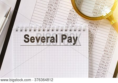 On The Table Are Financial Reports, A Pen, A Magnifying Glass And A Notebook With The Inscription -