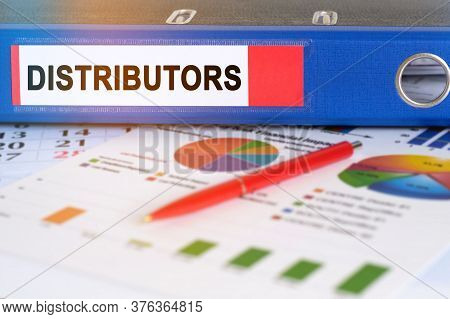 On The Table Are Pie Charts, A Pen And A Folder With The Inscription - Distributors. Business And Fi