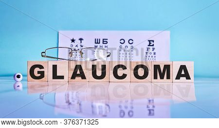 Glaucoma Word Written On A Wooden Cubes, Glasses, Eyes On The Background Of An Eye Test Table. Medic