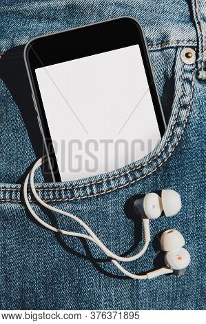 Mobile Phone With Blank Mockup Screen In The Pocket Of Blue Jeans With Headphones