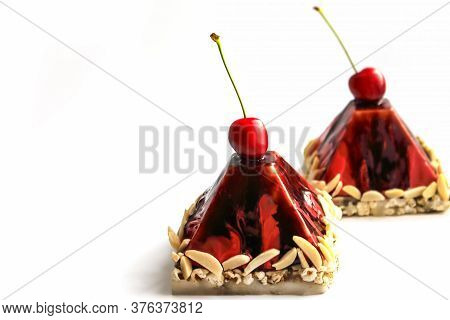 Dark Red Sweet Cherry Pyramid Desserts With Nuts On White Chocolate Mocha Tea Popcorn Bases Isolated