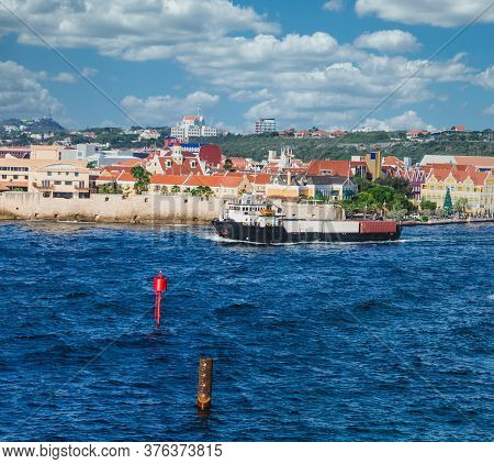 A Pilot Boat Guiding A Freighter Out Of The Harbor On Curacao