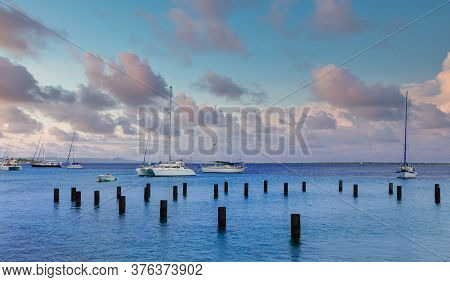 White Sailboats Beyond Wood Pilings In Bonaire