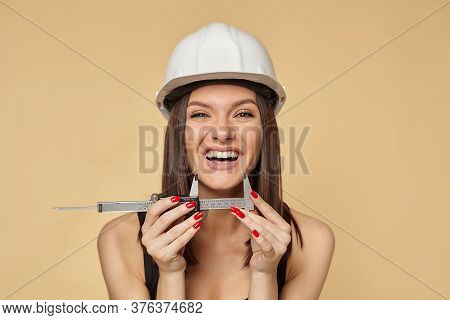 Construction Girl In A White Hard Hat And Protective Construction Mask Holding A Caliper. Makes The