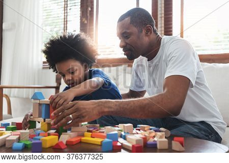 African Family Dad And Son Sitting Playing Game At Home Together. Happy Black Father And Kid Boy Bui