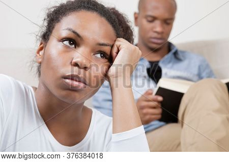 Sad young woman with man reading book in background