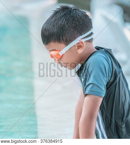 Little Boy With Swimming Goggles And Swim Suit Is Playing In Swimming Pool