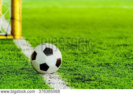 Classic Black And White Football Soccer Ball On Training Pitch Goal Line With Goal In The Background