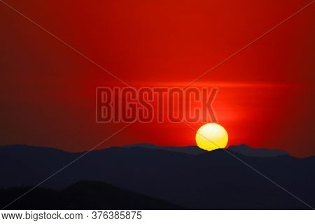 Sun Dawn On The Morning Sky Over Silhouette Dark Mountain And Clear Red Sky