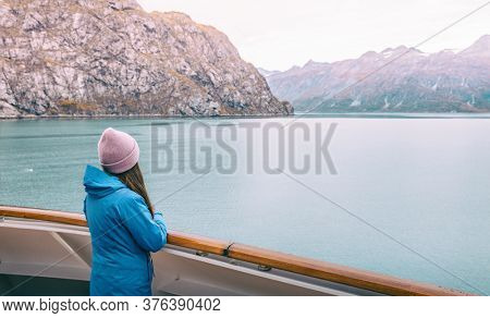 Alaska cruise Inside passage travel tourist woman looking at mountains landscape from balcony deck of ship. Glacier bay scenic vacation travel holiday.