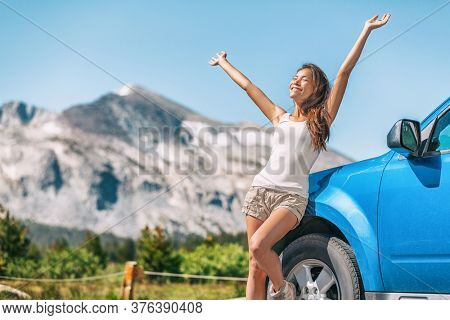 Happy road trip tourist girl enjoying driving sport car on summer travel adventure freedom vacation. Asian woman with open arms in freedom.