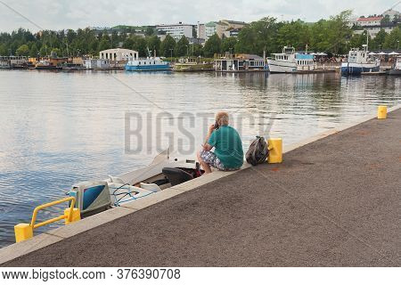 A Lonely Man Is Making A Phone Call Sitting On A Pier At Jyväskylä, Finland.