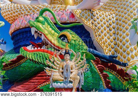 Religious Statue In A Buddhist Temple In Thailand. The Many-armed Statue Of The God On The Backgroun