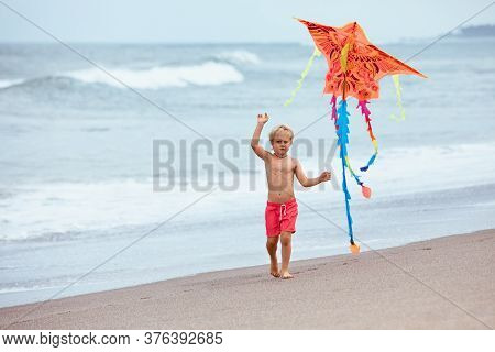 Happy Family Have Fun On Tropical Sea Beach Resort. Funny Baby Boy Run With Flying Kite Along Surf E