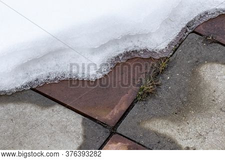 Snow Is Melting On The Footpath