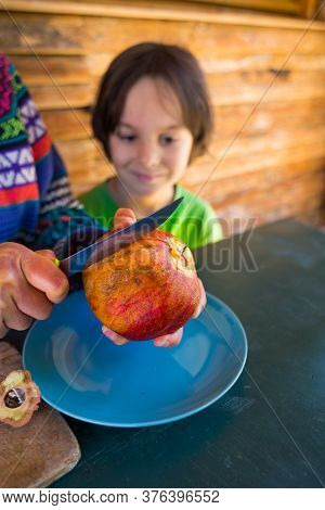 Ripe Juicy Pomegranate On A Blue Plate. The Child Watches As The Mother Cuts The Pomegranate.  Healt