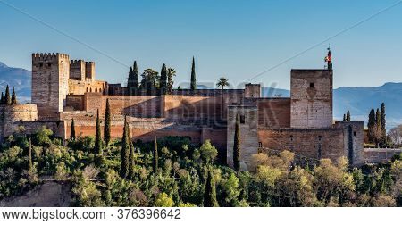View Of Alhambra Palace In Granada, Spain With Sierra Nevada Mountains At The Background