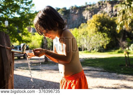 Tired Of The Heat, The Child Washes His Body With Water From A Tap In The Courtyard Of The House. Th