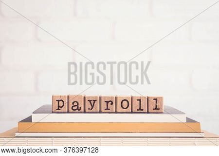 The Word Payroll, Letters On Wooden Cubes On Top Of Books With Bricks Background, Blank Copy Space,