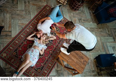 The Lovers Lie On A Carpet In Front Of The Fireplace And A Photographer To Make Photos. Honeymoon. P