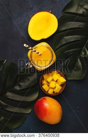 Mango Smoothie In Glass Jar With Fresh Fruit On Blue Background, Copy Space, Top View
