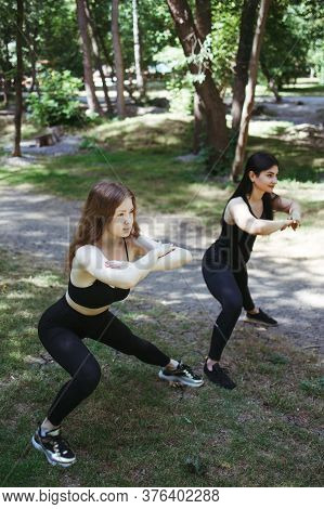 Fit Women Runners Doing Stretching Exercise, Preparing For Morning Workout In The Park. Street Fitne