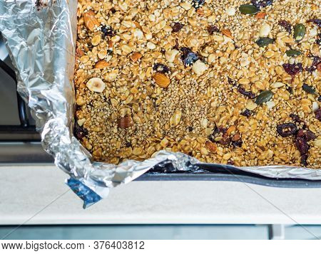 Home Made Energy Granola With Nuts, Dried Fruit, Peanut Butter And Superfoods Baked In Baking Tin.