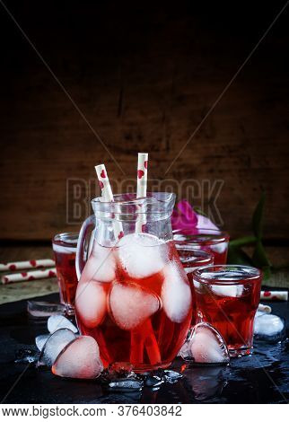 Red Drink In A Pitcher With Ice In The Shape Of Hearts, And Straws With Hearts On Old Wooden Backgro