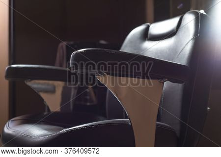 A Hairdressing Chair Made Of Brown Leather, Under A Ray Of Light, In A Barbershop, A Hairdressing Sa