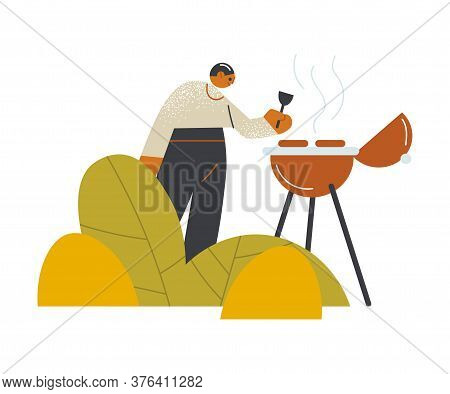 Young Man Making Barbeque Outdoors On Open Veranda Of Cafe